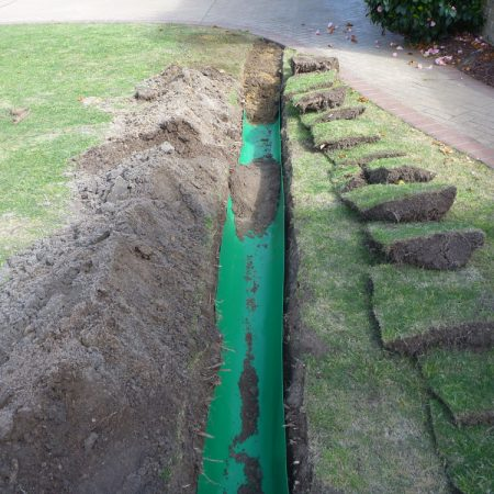 Root barrier laid in trench
